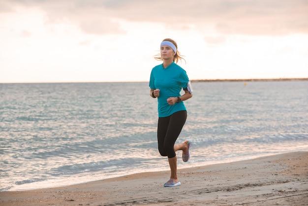 Jeune fille fit courir sur la plage au lever du soleil le matin