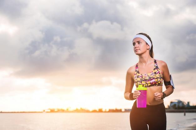 Jeune fille fit courir sur la plage au lever du soleil