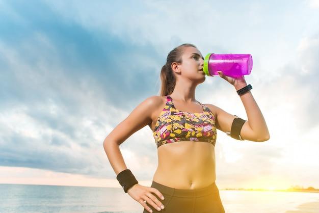 Jeune fille fit l'eau potable sur la plage après l'entraînement du matin