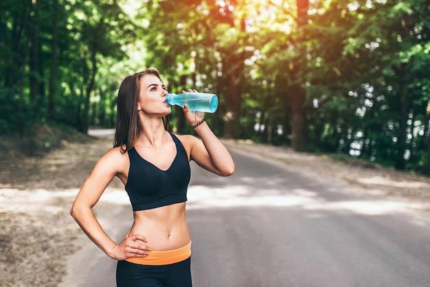 Jeune fille fitness, boire de l'eau dans le parc