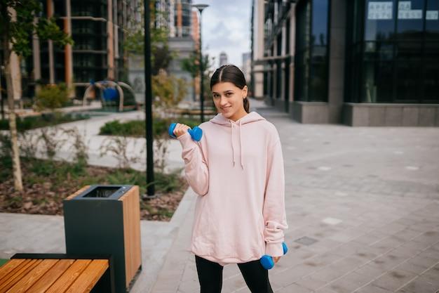 Jeune fille fitness faisant des exercices avec des haltères dans le parc de la ville