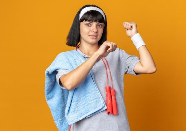 Jeune fille fitness portant un bandeau avec une corde à sauter autour du cou et une serviette sur une épaule serrant les poings à la confusion