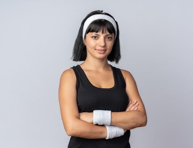 Jeune fille fitness portant un bandeau regardant la caméra avec une expression sérieuse et confiante avec les bras croisés debout sur blanc