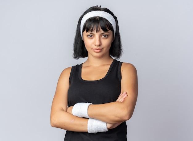 Jeune fille fitness portant un bandeau regardant la caméra avec une expression sérieuse et confiante, les bras croisés, debout sur fond blanc
