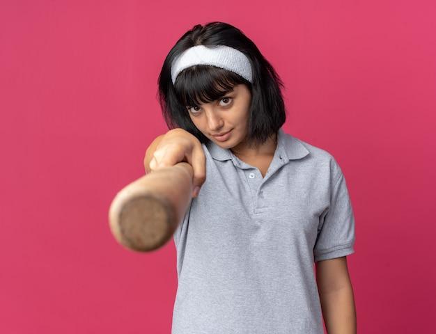 Jeune fille fitness portant un bandeau tenant une batte de baseball en regardant la caméra avec un visage sérieux debout sur rose