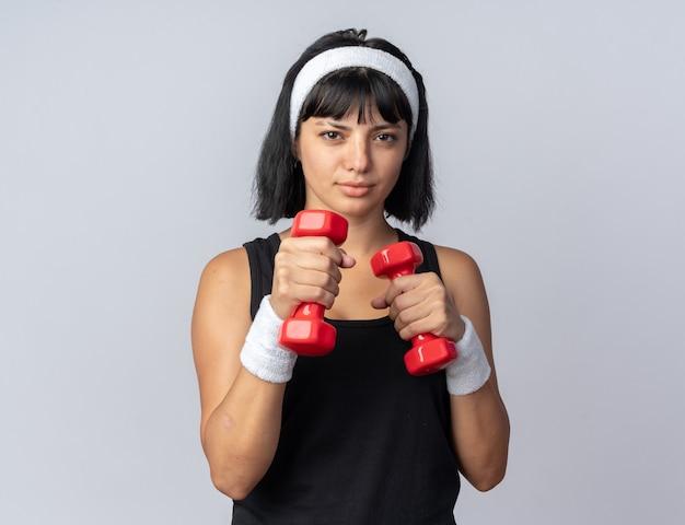 Jeune fille fitness portant un bandeau tenant des haltères faisant des exercices à la confiance debout sur blanc