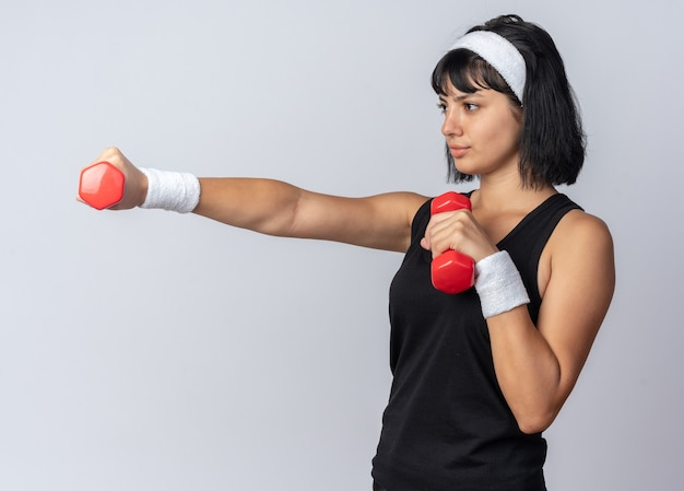Jeune fille fitness portant un bandeau tenant des haltères faisant des exercices à la confiance debout sur fond blanc