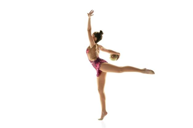 Jeune fille flexible isolée sur un mur blanc. modèle féminin adolescent en tant qu'artiste de gymnastique rythmique pratiquant avec de l'équipement. exercices pour la flexibilité, l'équilibre. grâce en mouvement, sport.