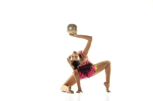 Jeune fille flexible isolée sur le mur du studio blanc