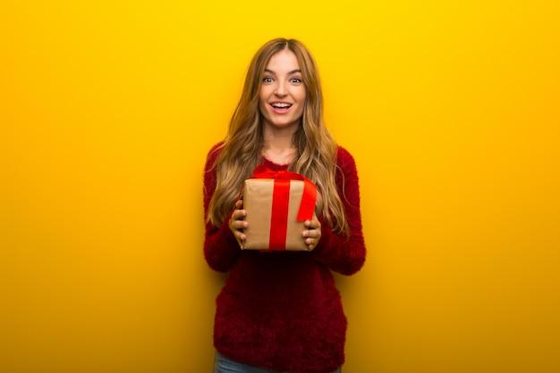 Jeune fille sur fond jaune vif surprise parce qu'un cadeau lui a été offert