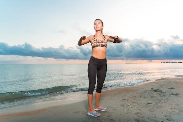 Jeune fille en forme, faire des exercices du matin sur la plage au lever du soleil