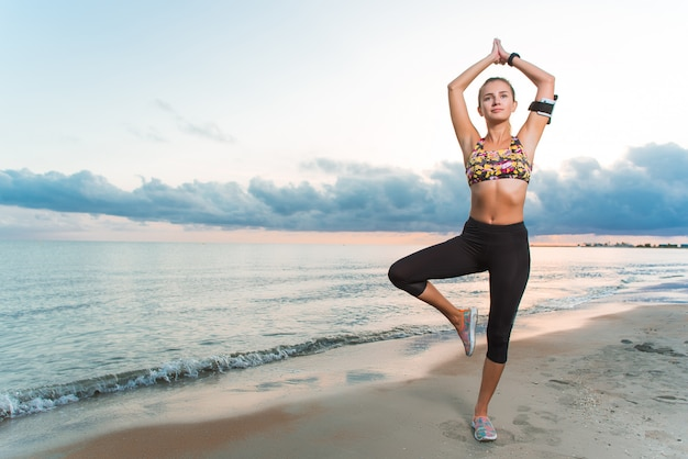 Jeune fille en forme, pratiquer le yoga sur la plage au lever du soleil