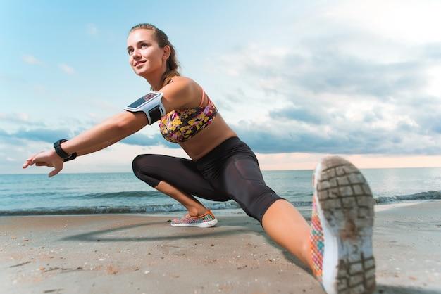 Jeune fille en forme qui s'étend sur la plage au lever du soleil