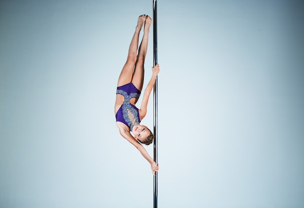 La jeune fille forte et gracieuse effectuant des exercices acrobatiques sur pylône