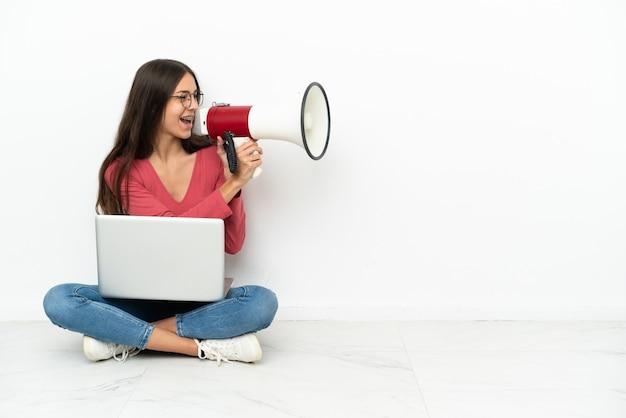 Jeune fille française assise sur le sol avec son ordinateur portable criant à travers un mégaphone
