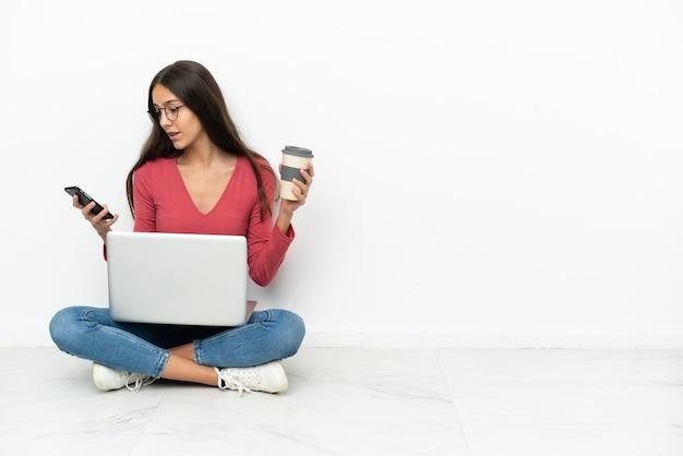 Jeune fille française assise sur le sol avec son ordinateur portable tenant du café à emporter et un mobile