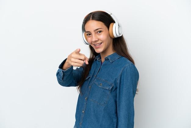 Jeune fille française isolée sur fond blanc à l'écoute de la musique et pointant vers l'avant