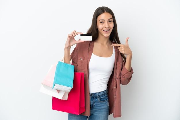 Jeune fille française isolée sur fond blanc tenant des sacs à provisions et une carte de crédit