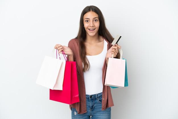 Jeune fille française isolée sur fond blanc tenant des sacs à provisions et surpris