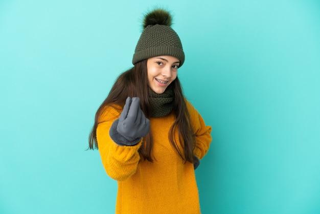 Jeune fille française isolée sur fond bleu avec un chapeau d'hiver faisant un geste d'argent