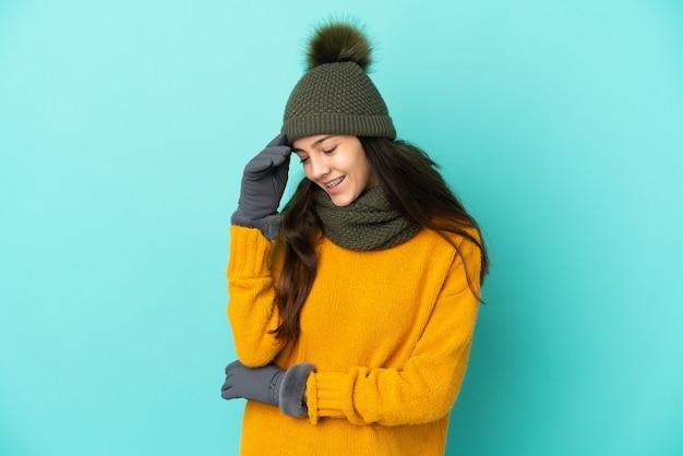 Jeune fille française isolée sur fond bleu avec chapeau d'hiver en riant