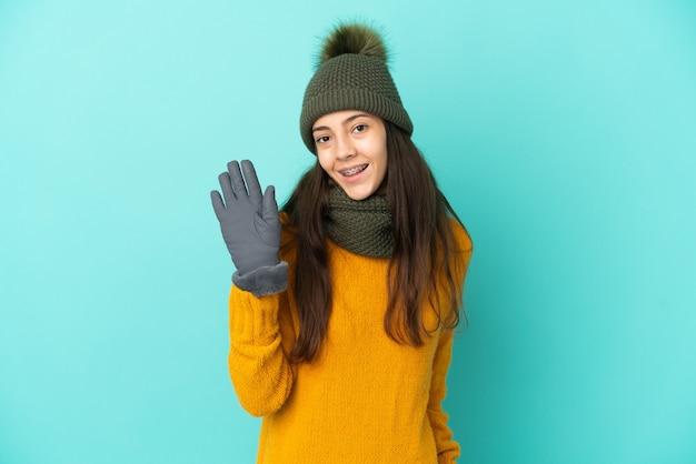 Jeune fille française isolée sur fond bleu avec chapeau d'hiver saluant avec la main avec une expression heureuse