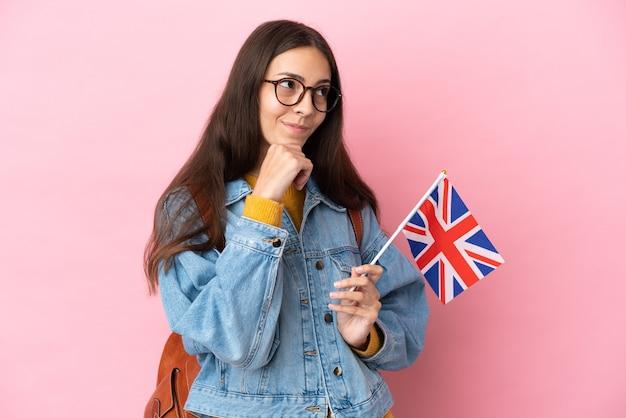 Jeune fille française tenant un drapeau du royaume-uni isolé sur fond rose et levant