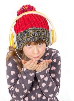 Jeune fille avec des gants et un bonnet de laine écoute de la musique avec un casque