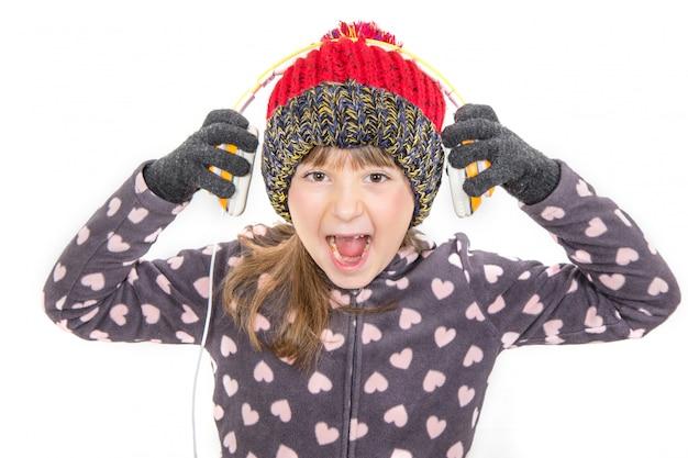 Jeune fille avec des gants et un chapeau en laine écoute de la musique avec un casque