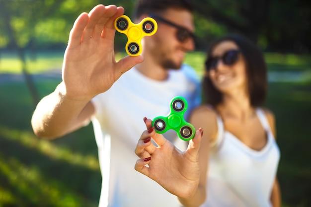 Jeune fille et garçon jouant avec une filature fidget dans le parc. jouet anti-stress. journée d'été ensoleillée. ils rient et sourient. bonne humeur.