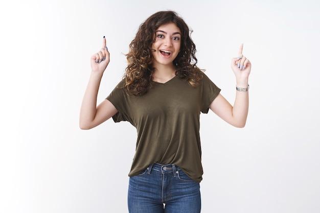Une jeune fille géorgienne créative excitée et excitée aux cheveux bouclés souriante vous encourage à essayer le produit pointant l'index vers le haut pour promouvoir une publicité cool, fond blanc
