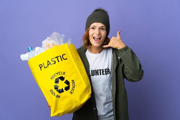 Jeune fille géorgienne tenant un sac plein de bouteilles en plastique à recycler en faisant un geste téléphonique. rappelle-moi signe