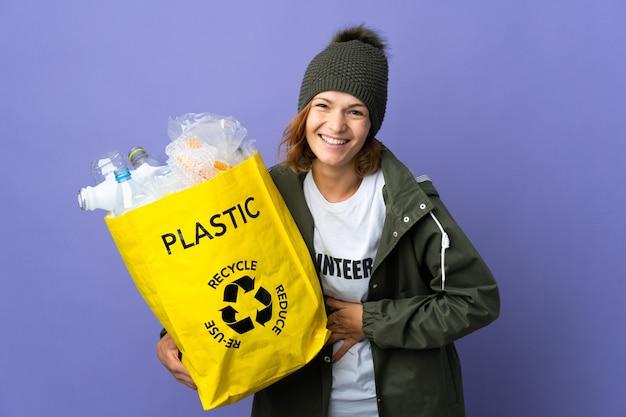 Jeune fille géorgienne tenant un sac plein de bouteilles en plastique à recycler en souriant beaucoup