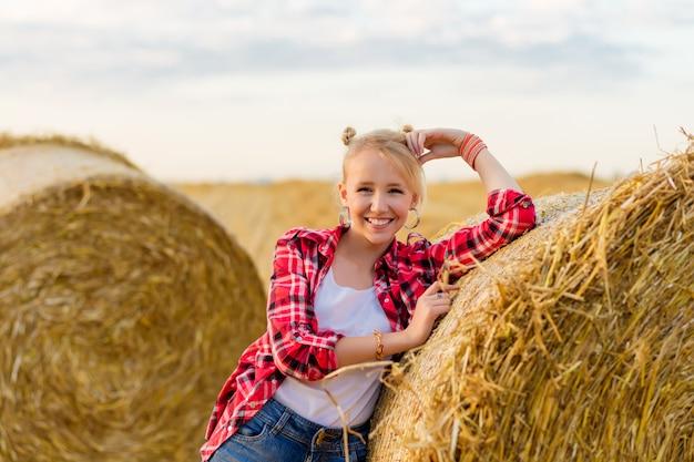 Jeune fille sur des gerbes de paille dans un champ.
