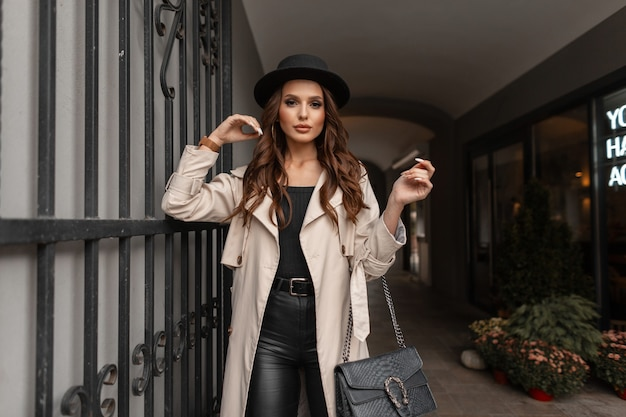 Jeune fille glamour aux cheveux bouclés avec un chapeau dans un manteau gris à la mode avec un sac à main en cuir noir dans la rue. style et beauté d'automne féminin
