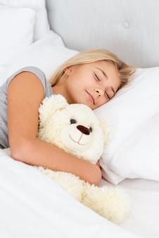 Jeune fille glissant avec son ourson en jouet