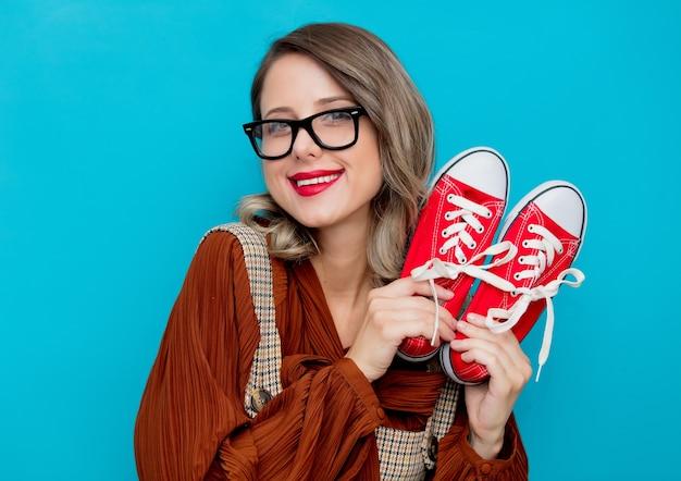 Jeune fille avec des gommes rouges sur bleu