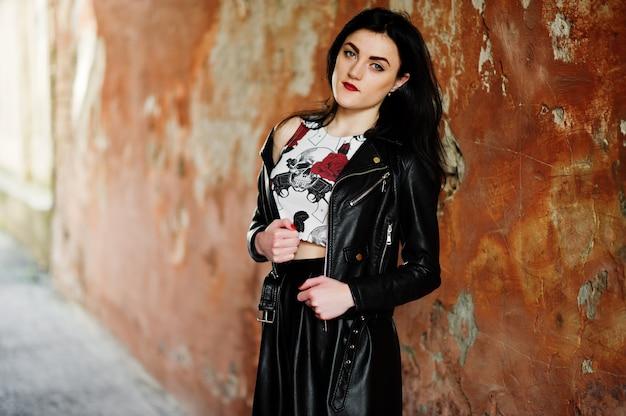 Jeune fille goth sur jupe en cuir noir et veste contre le mur de grunge.
