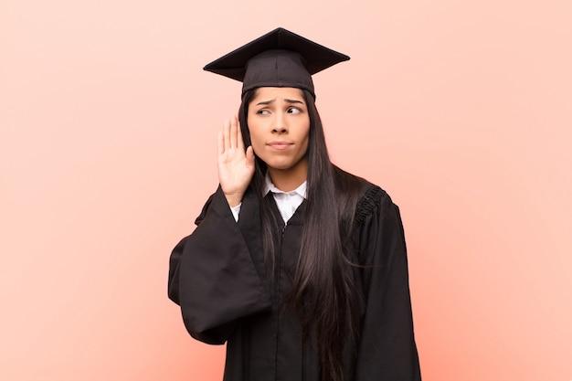 Jeune fille en graduation robe essayant d'entendre une conversation secrète
