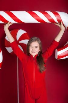 Jeune fille avec une grosse canne à sucre de noël