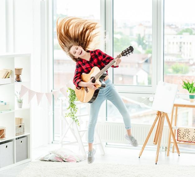 Jeune fille avec guitare en saut