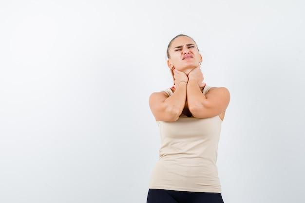 Jeune fille en haut beige, pantalon noir tenant les mains sur le cou, ayant des douleurs au cou et regardant harcelé, vue de face.