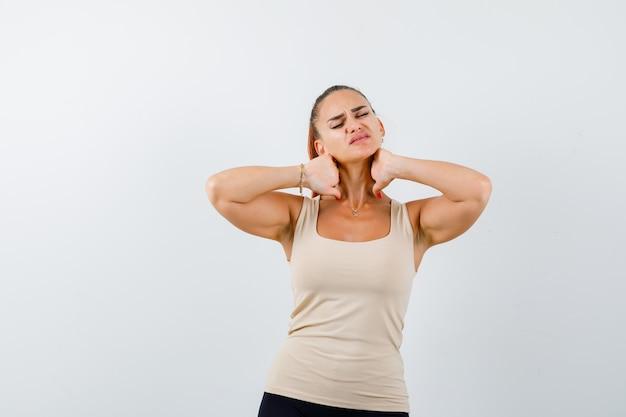 Jeune fille en haut beige, pantalon noir tenant les mains sur le cou, ayant des douleurs au cou et à la vue ennuyée, de face.