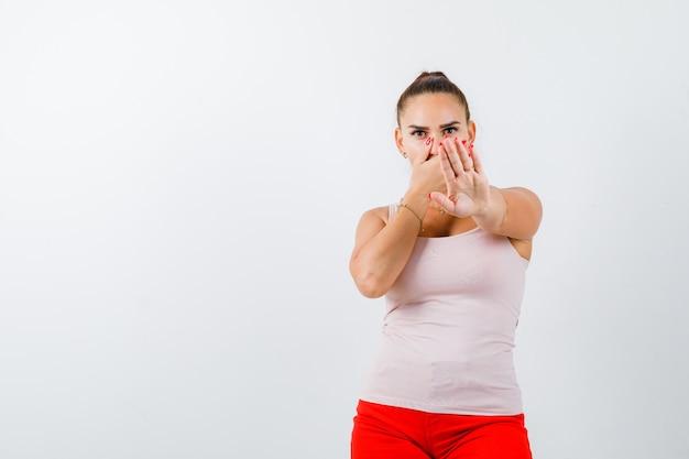 Jeune fille en haut beige et pantalon rouge couvrant la bouche avec la main, montrant un panneau d'arrêt et regardant sérieusement, vue de face.