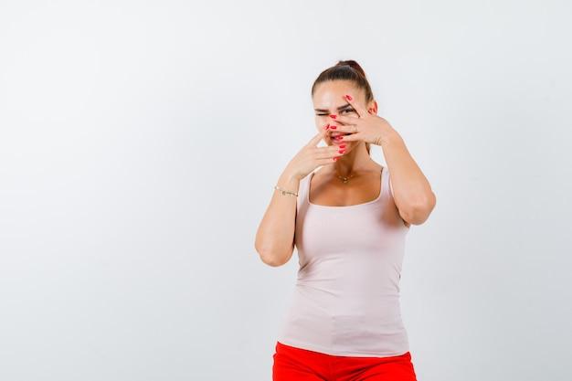 Jeune fille en haut beige et pantalon rouge regardant à travers les doigts et regardant sérieusement, vue de face.