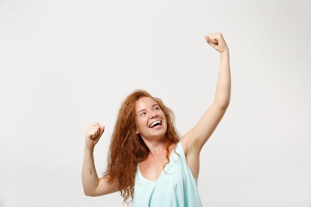 Jeune fille heureuse de femme rousse dans des vêtements légers décontractés posant isolé sur fond blanc. concept de mode de vie des émotions sincères des gens. maquette de l'espace de copie. serrant les poings comme un vainqueur, levant les mains.
