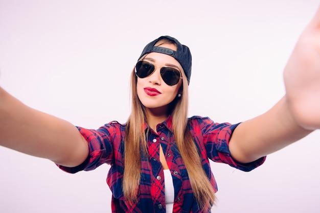 Jeune fille heureuse sourire prendre selfie sur mur blanc