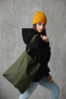 Une jeune fille hipster dans un sweat à capuche noir et un chapeau jaune avec un sac shopping devant le mur.