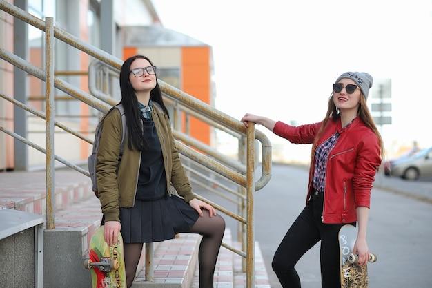 Une jeune fille hipster fait du skateboard. copines de filles pour une promenade en ville avec une planche à roulettes. sports de printemps dans la rue avec une planche à roulettes.