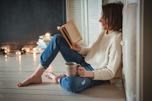 Jeune fille hipster lit un livre à la maison. formation, l'étudiant se prépare à l'examen. vieux livre rareté antique. espace libre. carton enduit avec cadres. place pour la mise en page du texte